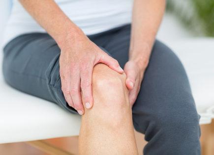 Frau mit Schmerzen im Knie